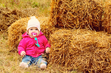 baby girl in fall time sitting near the hay photo