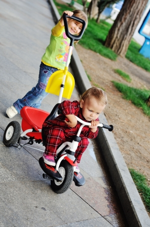 toddler girl walking with baby sister on the tricycle