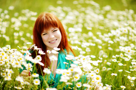 redhead  young woman in the feild of daisies (soft focus effect)  photo