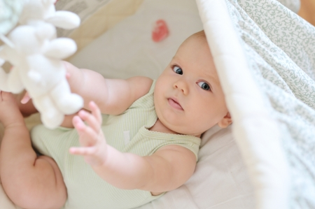 early childhood: baby playing toys in crib