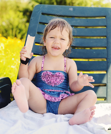 cute toddler girl sitting on sun lounger and eating crisp bread photo