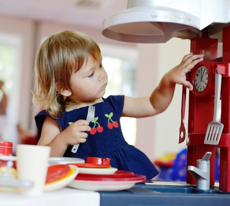 toddler girl playing toy kitchen photo