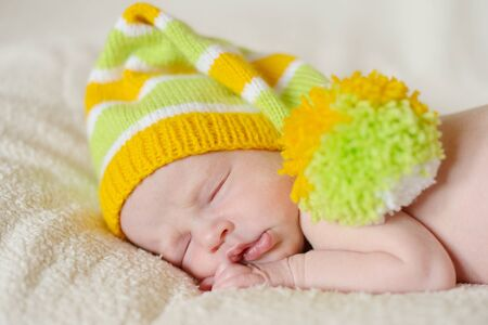 sleeping newborn wearing funny hat photo