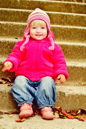 lovely toddler sitting on the stairs photo