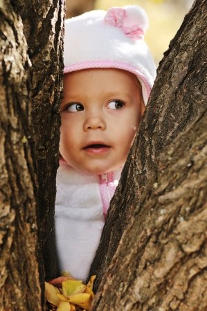 peek-a-boo  - toddler girl hiding between trees photo