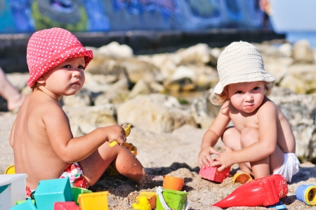 baby girls playing with sand on the beach photo