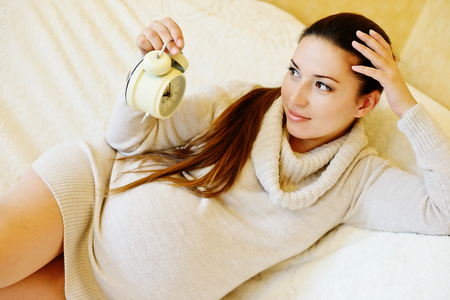 8 9 months: pregnant woman with clock on the sofa
