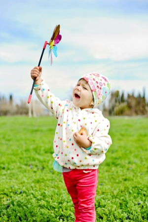 toddler girl with windmill in spring day photo
