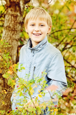 boy in fall time in forest photo