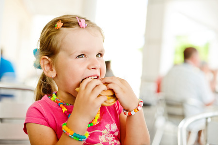 little girl eating a hamburger photo