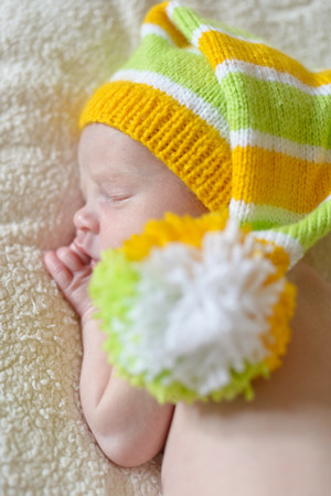 sweet newborn wearing hat with big pompom photo