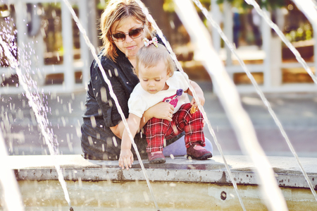 Woman with child playing against splashes of water photo