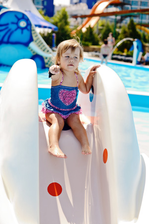 cute toddler on the water slide in aqua park photo