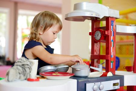 toddler girl playing toy kitchen