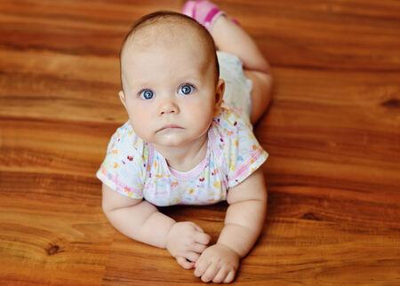 bebe gateando: bebé tirado en el piso de madera