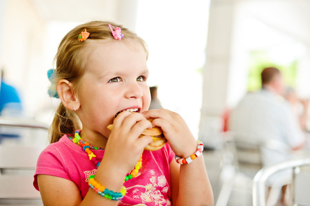little girl eating a hamburger Stock Photo - 27626721