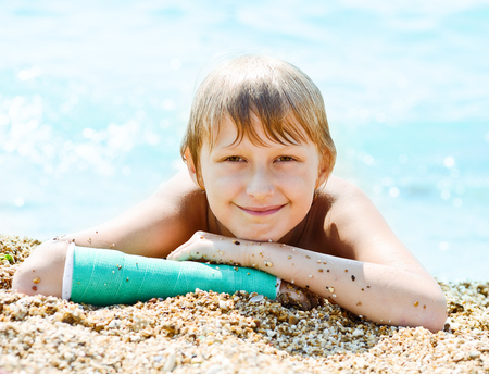 broken arm: boy with cast on hand laying on the beach