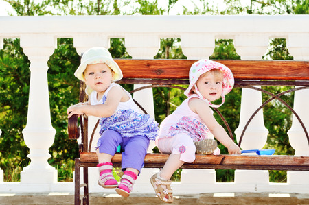 two babies sitting on the bench photo