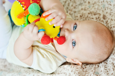 sweet baby biting a toy photo