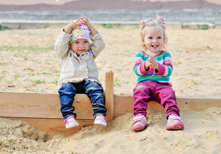 happy toddlers sitting in sand photo