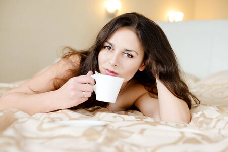 brunette young woman enjoying coffee in bed photo