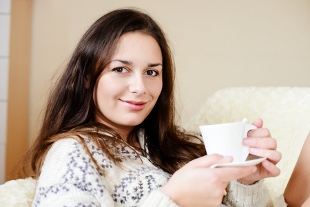brunette with cup of coffee at home photo