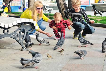 family feeding doves in city photo