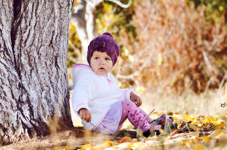 cute  baby girl sitting under the tree photo