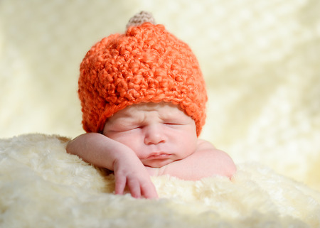 sleeping newborn wearing pumpkin hat photo