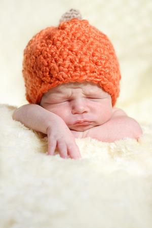 sleeping newborn wearing pumpkin hat photo