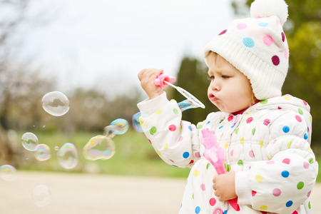 cute toddler girl blowing   soap bubbles photo