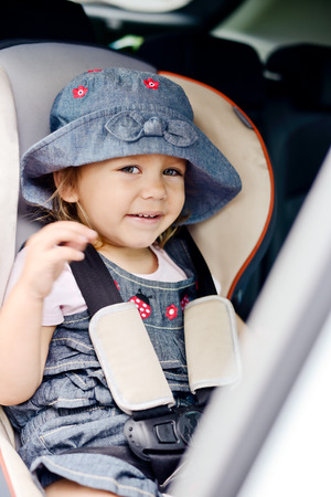 happy  toddler girl  in car seat photo