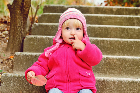 baby girl picking her nose outdoors photo