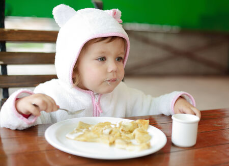 toddler girl eating in outdoor cafe photo