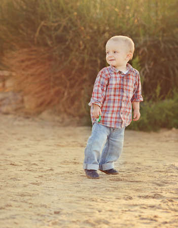 playful toddler boy on the beach photo