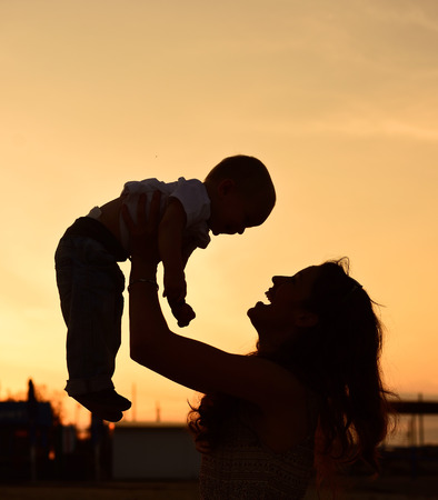 Mother and baby son silhouettes on beach at sunset photo