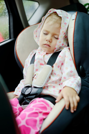 toddler girl sleeping in car seat photo