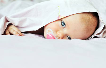 3 months old baby looking out under the blanket Stock Photo - 27792227