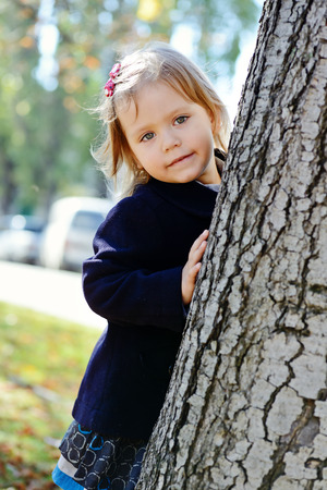 sweet toddler girl hiding behind the tree photo