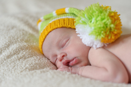 sleeping newborn wearing funny striped hat photo
