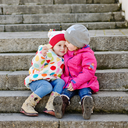 two toddler friends sitting on the stairs photo