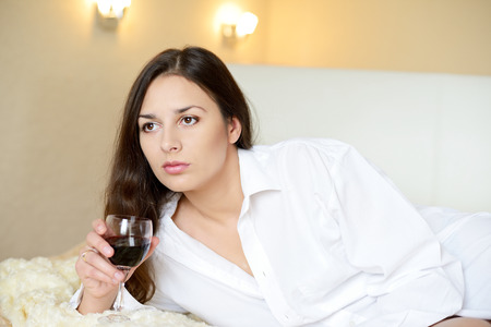 brunette with glass of wine at home photo