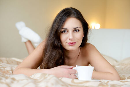 pretty brunette enjoying coffee in the bed photo