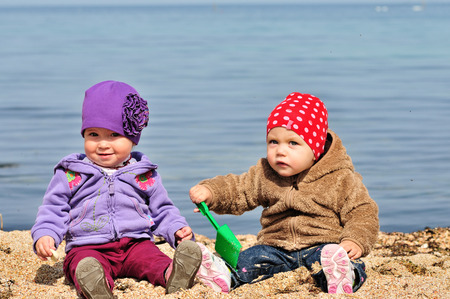 two baby friends playing on the sea shore photo