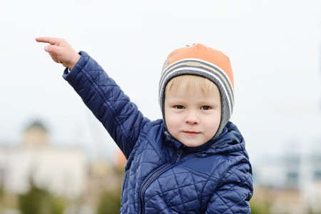 toddler boy is pointing on the left  outdoors photo