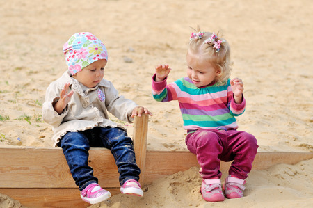 happy toddlers playing in sand photo
