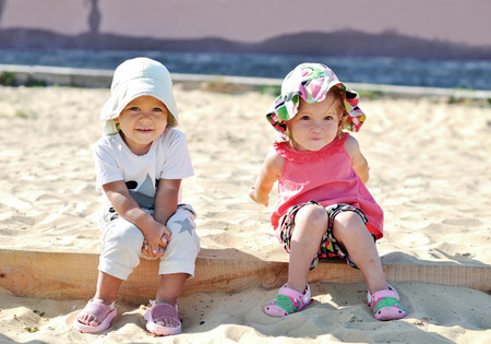 toddler girls playing in sand photo