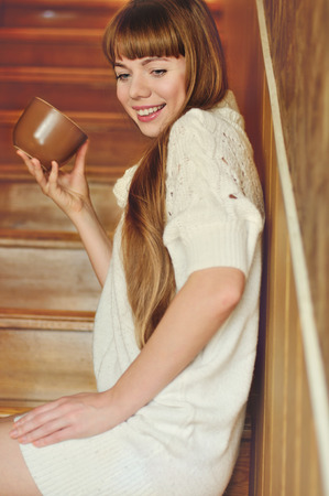 girl with mug of hot drink on the stairs photo