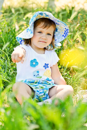 two years old summer toddler girl pointing with finger photo
