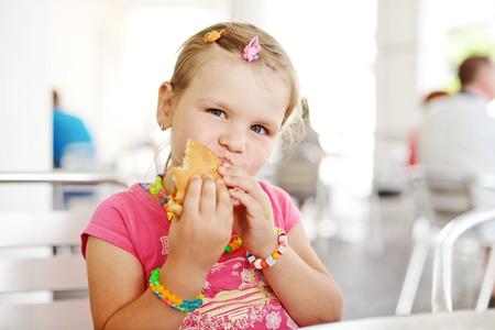 little girl eating a hamburger photo